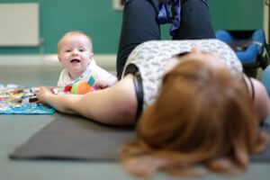baby and mum lying down at a pilates class.