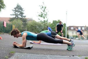 Lady doing a plank exercise at an outside exercise class outdoors bootcamp..