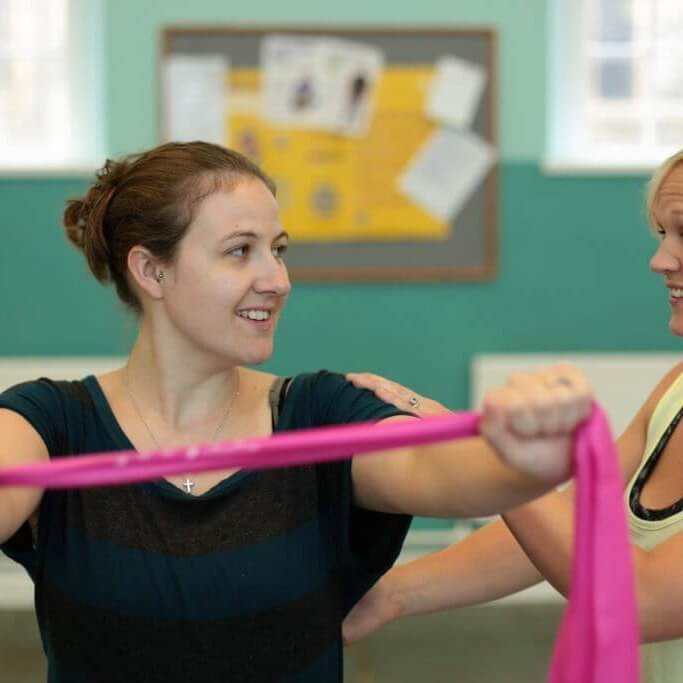 Charlotte and client with a pink exercise band.