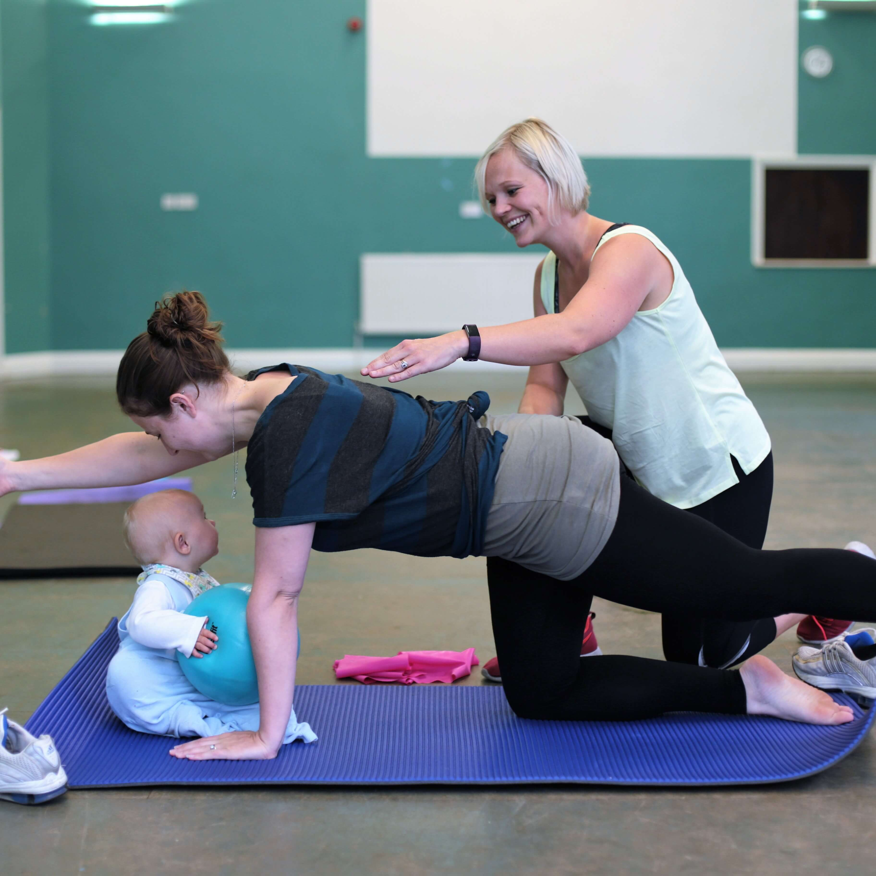 Exercising at a pilates class with baby watching.