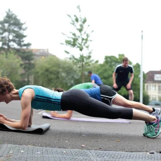 Lady doing a plank exercise at an outside exercise class.