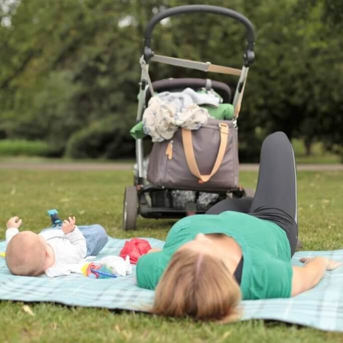 Buggyfit session outside with baby on a mat and a buggy in background.